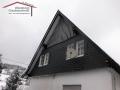 Fassadengestaltung mit Holzdeckelschalung sowie Naturschiefereindeckung im Format 20x20 als Wabendeckung